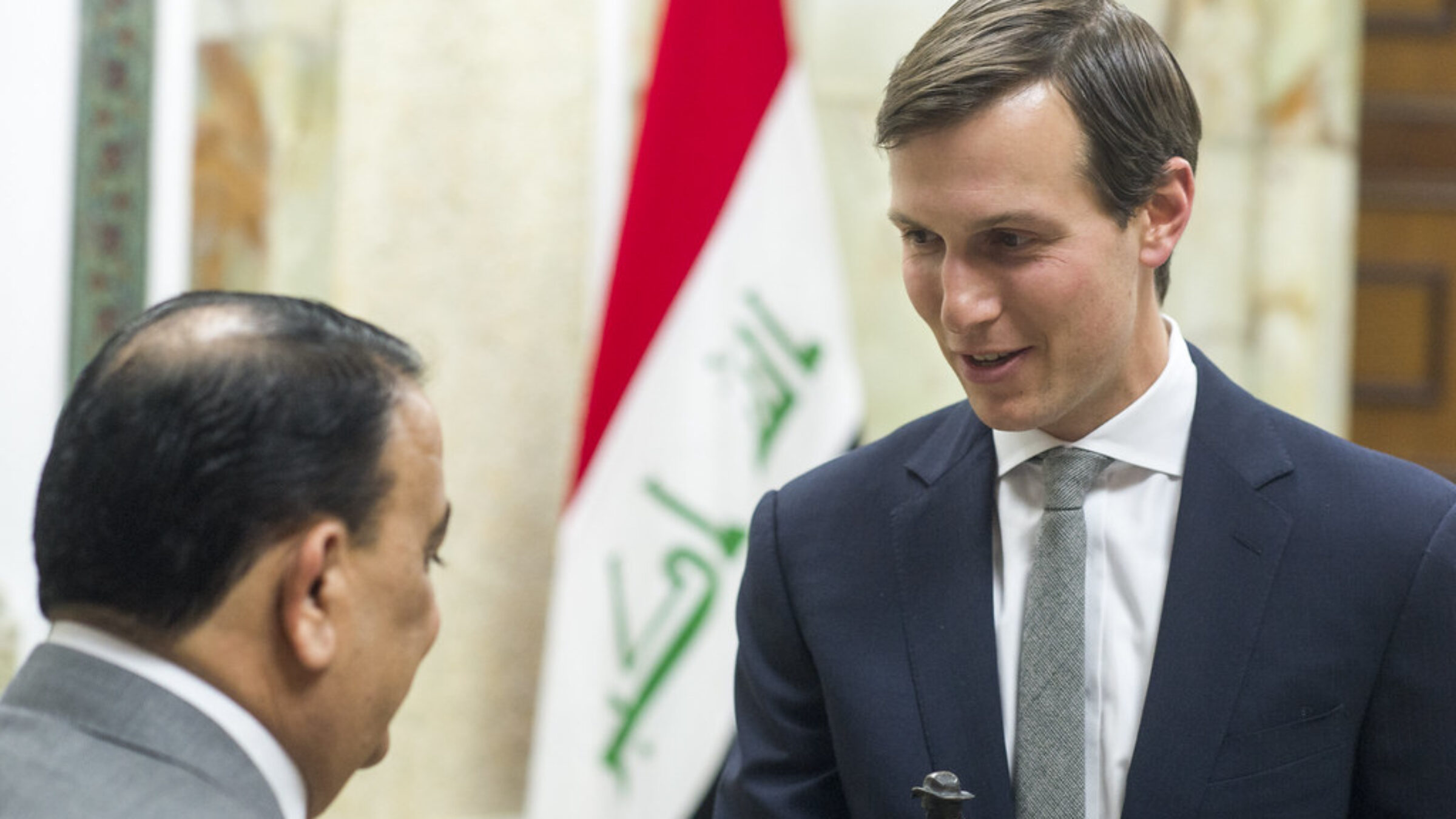 Jared Kushner speaks to someone with the Iraqi flag in the background