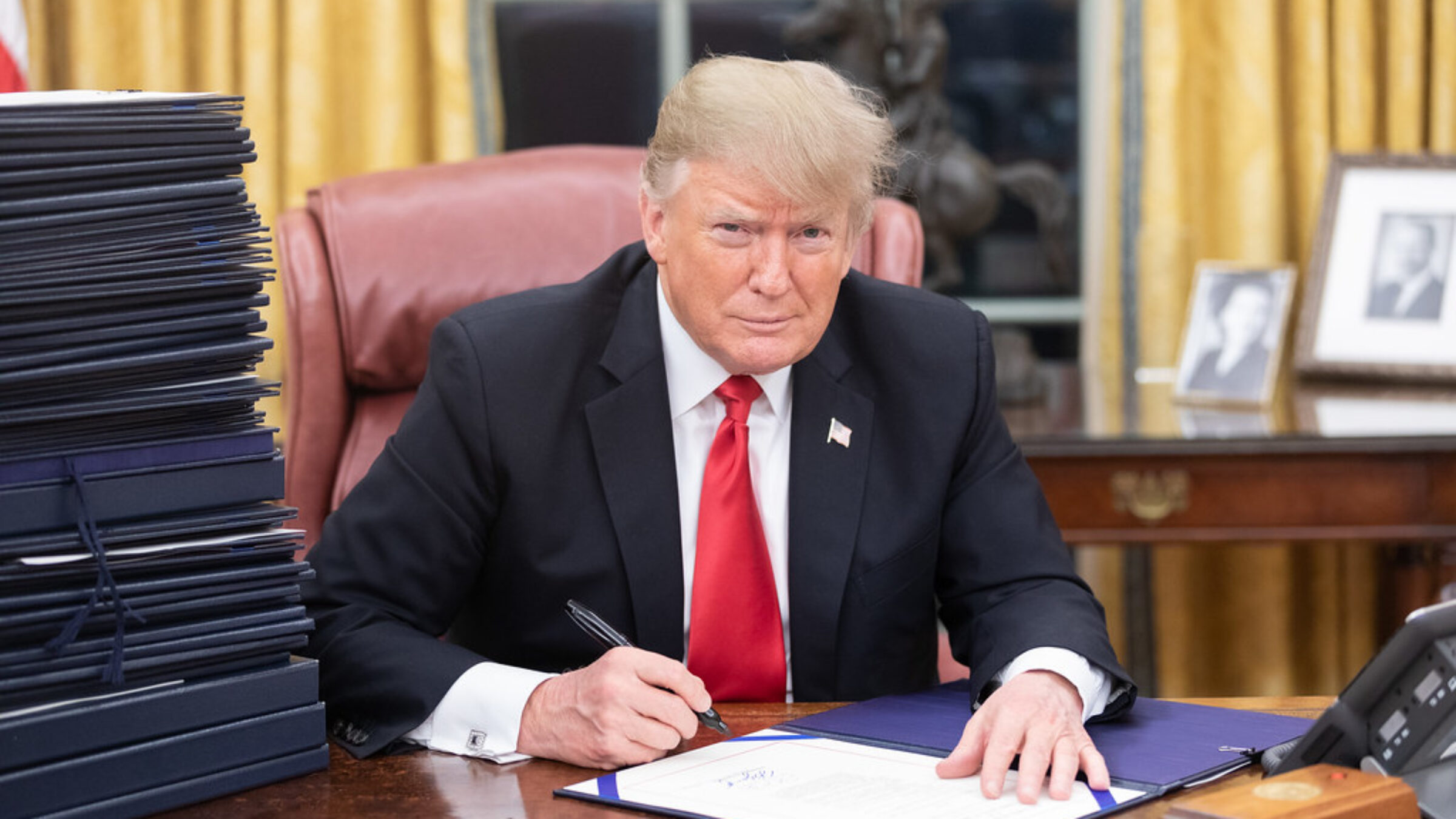 A straight-faced Donald Trump signs a document in the Oval Office