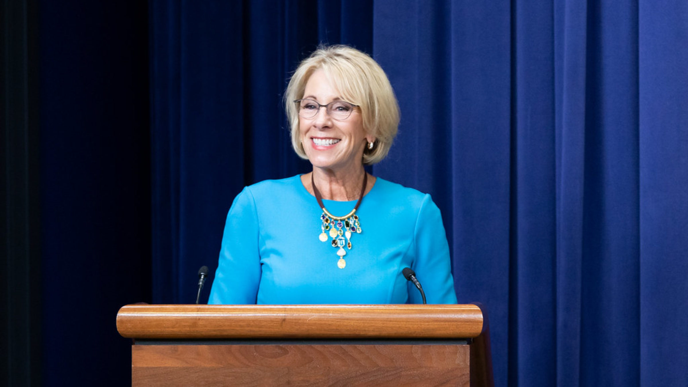 Betsy DeVos smiles while at a podium