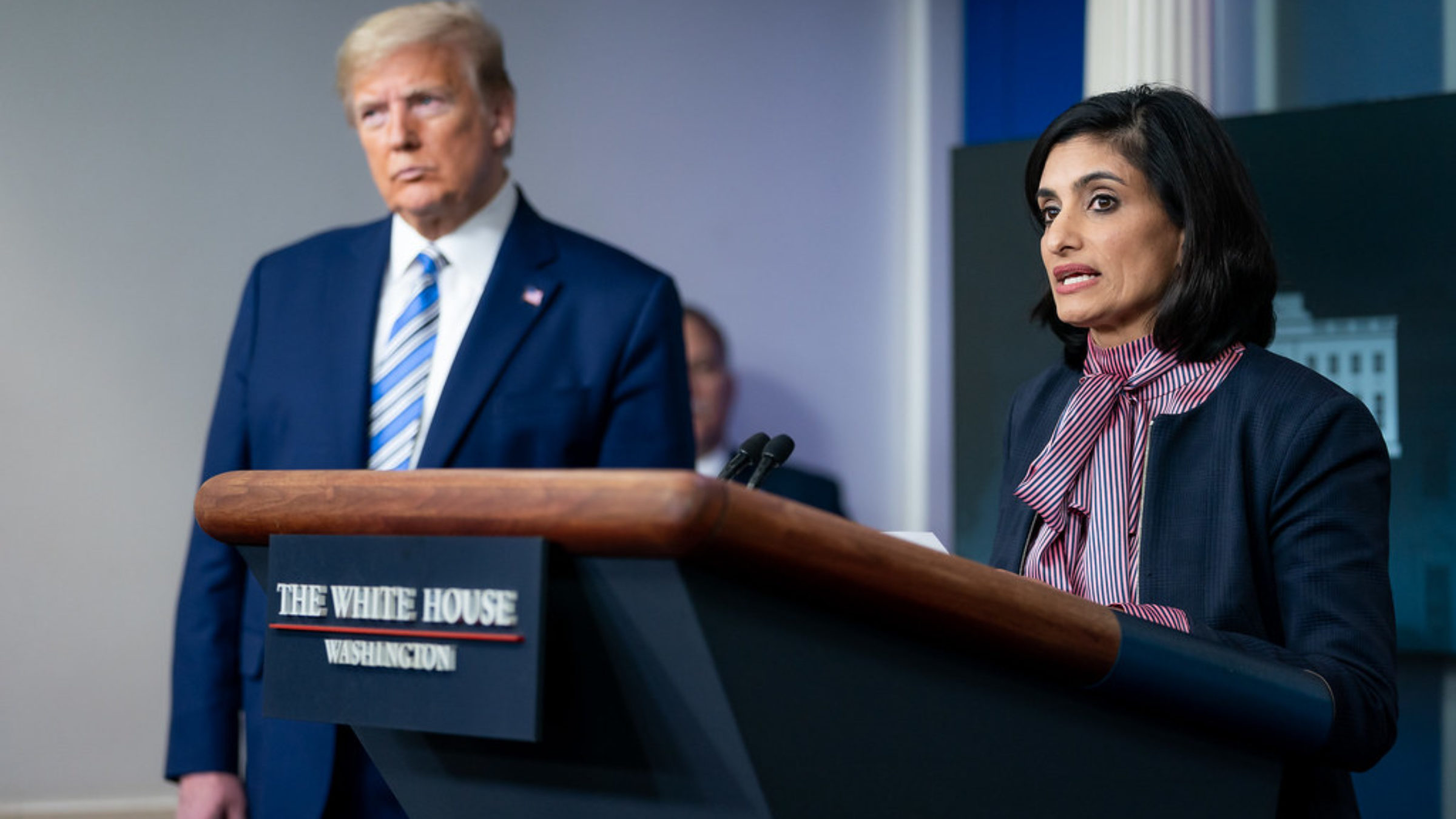 CMS Administrator Veema Serma speaks at a podium at a press briefing while Donald Trump looks on